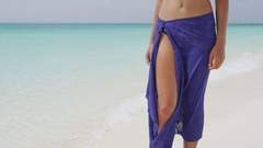 Blue pareo woman legs standing in sand on tropical beach vacation Stock Footage