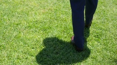 Groom in stylish retro shoes walks on green grass lawn. Back view Stock Footage