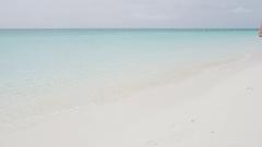 Elegant woman walking on pristine beach Stock Footage
