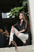Petite young woman with very long hair wear heels white pants bodysuits and.. Stock Photos