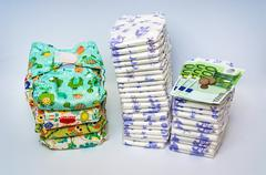 Compare reusable cloth diapers with pile of disposable diapers Stock Photos