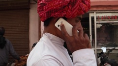 Rajasthani young male in red turban walking and talking on the cell phone mobile Stock Footage