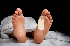 The dead man's body with blank tag on feet under white cloth in a morgue Stock Photos