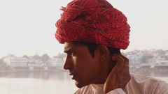 Portrait of a handsome Rajasthani man sitting by the holy Pushkar Lake in India  Stock Footage