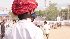 Indian man with red turban turns and is wearing a pollution mask at a Fairground Stock Footage