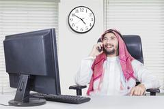 Arabian man smiles with smartphone Stock Photos