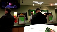 People at a bank counter talking to the teller inside TD Bank Stock Footage