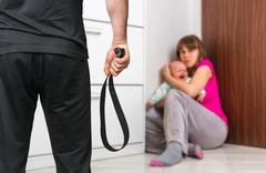 Aggressive man with a leather belt is abusing his wife and crying baby Stock Photos