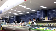 Seafood clerk stocking fish and chatting to co-worker Stock Footage