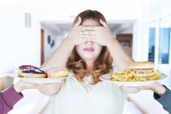 Fat woman closed eyes for junk food Stock Photos