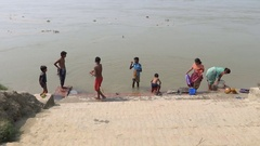Indian women washing clothes and children playing on the holy river Ganges Stock Footage