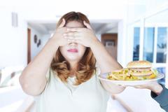 Woman refusing hamburger and french fries Stock Photos