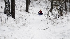 Kids have fun sledding with snow slides Stock Footage