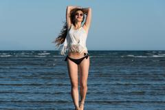 Woman with long curly hair wear bottom bikini, sunglasses and white shirt, .. Stock Photos