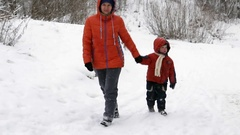 A woman with a child 3 years old is walking in the winter on snow Stock Footage