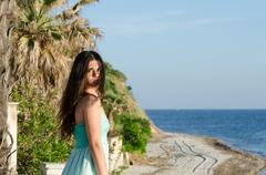Beautiful lady standing on veranda of a beachfront home, palm trees and oce.. Stock Photos