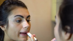 Girl paints her lips in the bathroom Stock Footage