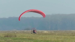 Motorized paraglider takes off on airfield Stock Footage