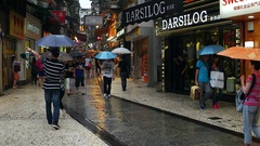 Macao - People with umbrellas walking in Historic Centre of Macao in rainy day. Stock Footage