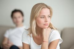 Serious sad woman thinking over a problem, man sitting aside Kuvituskuvat