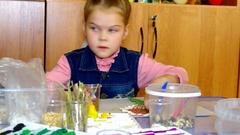 Girl sticks seeds on crafts Stock Footage