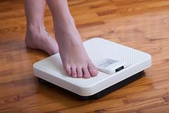 Womans feet and time for weight truth from a scale Stock Photos