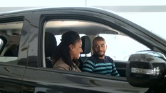 Young African couple choosing a car at the car salon Stock Footage