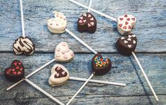 Many Cake Pops in the form heart lie on the old blue wooden background top vi Stock Photos