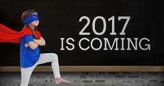 Girl in superhero costume standing near a board with 2017 new year quotes Stock Photos