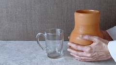 Milk is poured into a glass from a clay pot_Side view Stock Footage