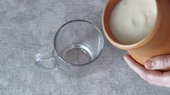 The woman pours milk from a pitcher into a glass Stock Footage