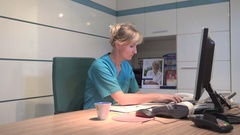 Yong receptionist typing on comuter has a headache. Steadicam shot. Stock Footage