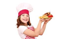 Happy little girl cook with roasted chicken wings on plate Stock Photos
