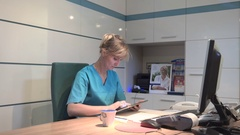 Young receptionist coping data from tablet to documents. Steadicam shot. Stock Footage