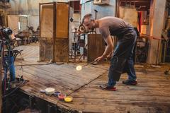 Glassblower attaching colored glass to a piece of hot molten glass Stock Photos
