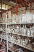 Empty glassware arranged on shelf in workshop Stock Photos