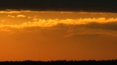 Low overcast and atmospheric haze have painted a sunset in red tone. Stock Footage