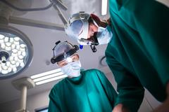 Surgeons wearing surgical loupes while performing operation Stock Photos