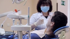 Dentist checks teeth of male patient by dental mirror Stock Footage