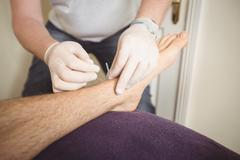 Physiotherapist performing dry needling on the leg of a patient Stock Photos