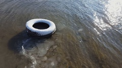 Old tire under snow in river sand in winter time. Stock Footage