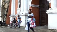 People pass by Disabled beggars beg at church portal Stock Footage