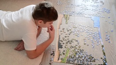 Teen boy collects a puzzle lying on floor Stock Footage
