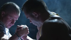 A couple of muscular man measuring forces. Arm-wrestling in the gym Stock Footage