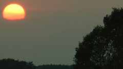 Dense clouds and atmospheric haze have hidden the sun during a sunset. Stock Footage