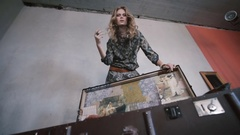 Beautiful blonde girl throws stuff from a vintage suitcase Stock Footage