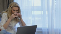 Woman holds a cup of tea in her hand at home Stock Footage
