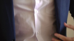 Young man dressed in the celebration, Groom buttons his jacket Stock Footage