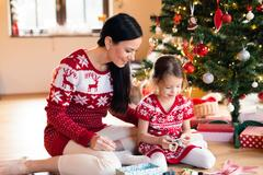 Young mother with daugter at Christmas tree at home Stock Photos