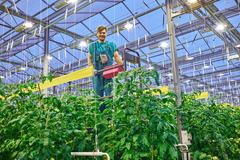 Friendly farmer working on hydraulic scissors lift platform in g Stock Photos